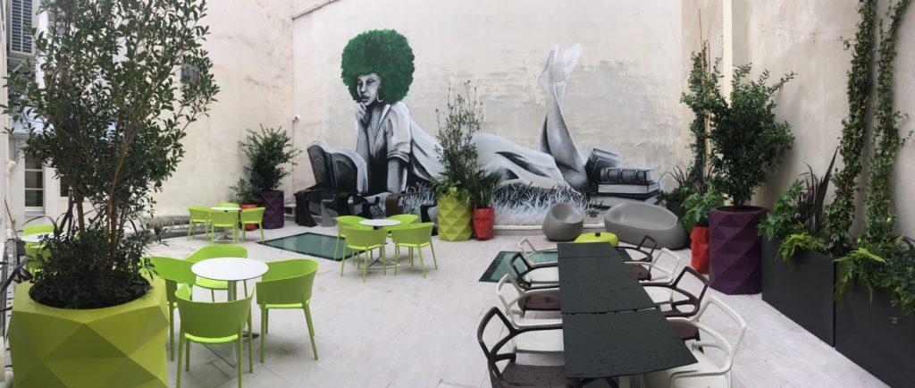 Graffiti sur terrasse de bureau végétalisée avec des plantes en pot
