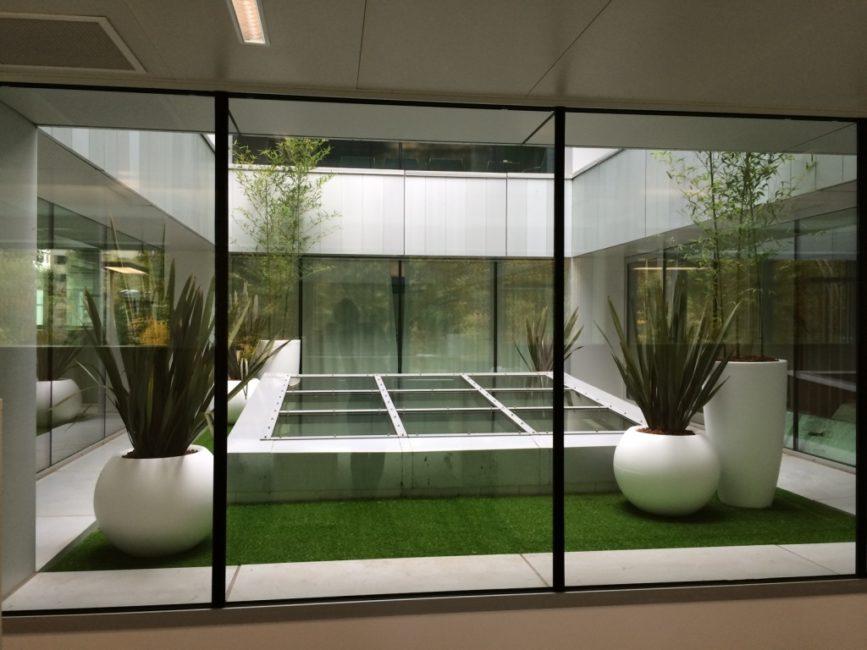 Patio avec gazon synthétique et plantes en bac