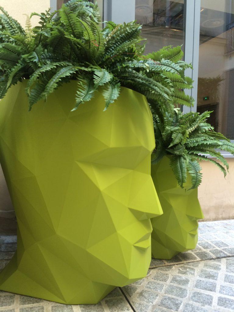 Plantes dans des pots en forme de tête sur une terrasse